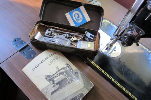 The original sewing machine manual and accessories tin.